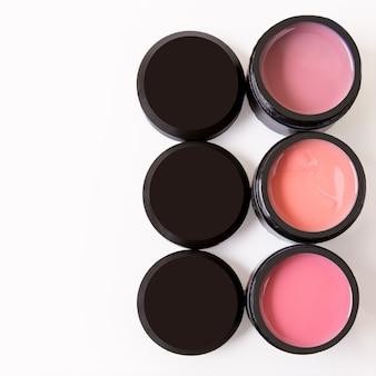 Cosmetici per il rivestimento colorato per la cura delle mani per la lamina ungueale in dosi nere su sfondo bianco