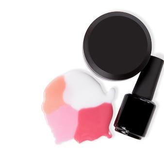Cosmetici per gel per unghie in diversi contenitori neri su una superficie bianca hanno versato smalti per unghie su sfondo bianco white