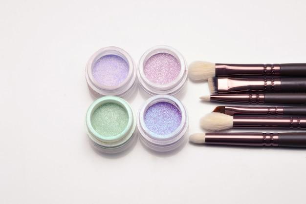 Cosmetici. trucco. vasetti con ombre luminose friabili, glitter. colori rosa, verdi, lilla su sfondo lilla. avvicinamento. spazio per testo o design.