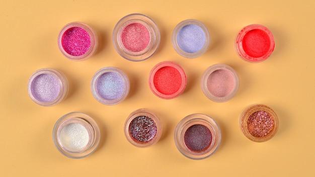 Cosmetici. trucco. vasetti con ombre luminose friabili, glitter. colori rosa, pesca, dorati su fondo beige. avvicinamento. spazio per testo o design.