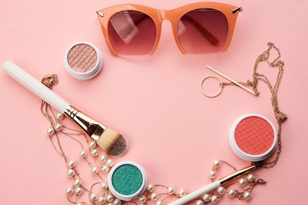 Cosmetici su sfondo rosa ombretto pennello polvere arrossire orologio