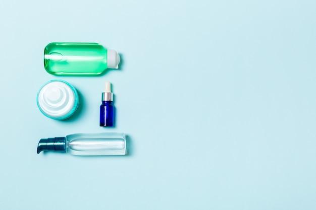 Marchio spa cosmetics, vista dall'alto con spazio di copia. set di tubi e vasetti di crema piatto giaceva su sfondo blu