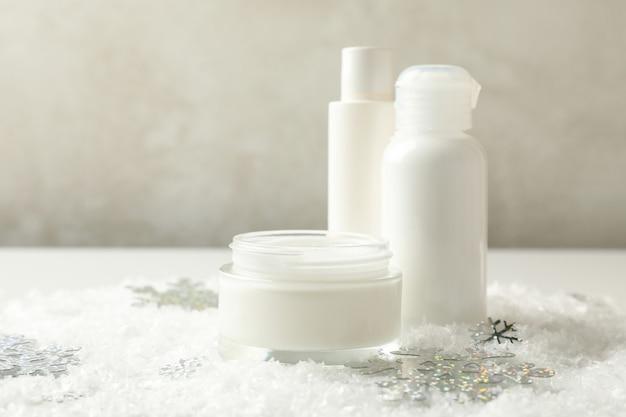 Cosmetici sul tavolo bianco con neve decorativa