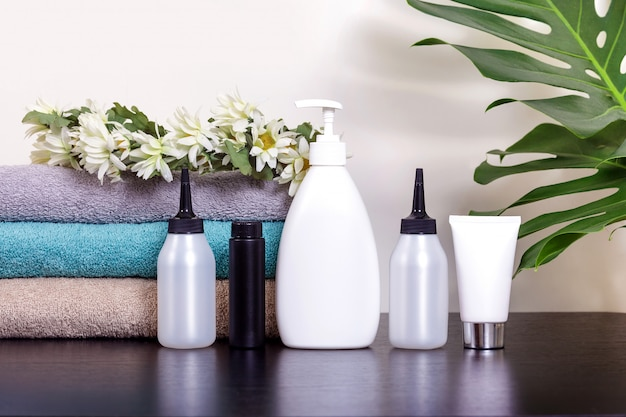 Cosmetici in tubi bianchi e prodotti da bagno su un tavolo nero con foglie tropicali.