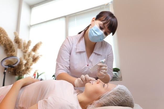Il cosmetologo applica l'anestesia prepara le labbra del cliente per la procedura di iniezione di acido ialuronico