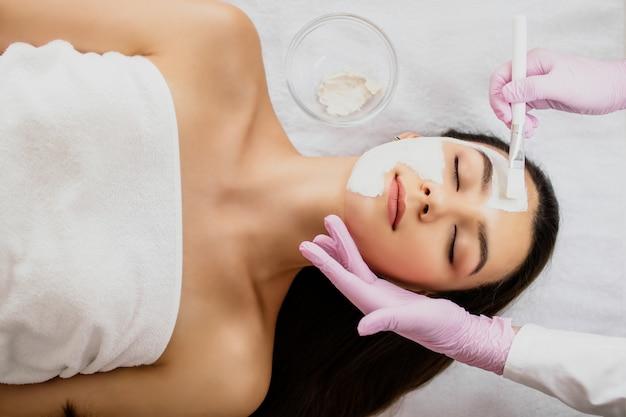 Il cosmetologo applica una maschera all'argilla bianca sul viso della ragazza con un pennello bianco