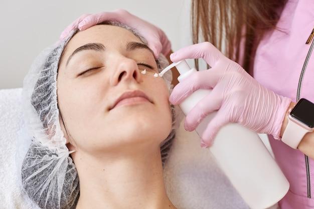 Il cosmetologo applica una maschera idratante sul viso femminile dalla grande bottiglia bianca. giovane donna sdraiata rilassante, con gli occhi chiusi su couh