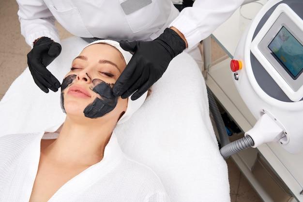 Cosmetologo applicando maschera nera sul viso di una bella donna per la buccia del carbonio