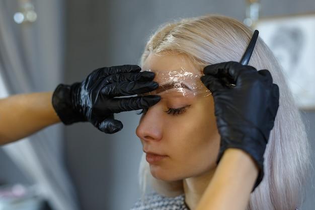 Cosmetologo che applica trucco permanente sulle sopracciglia-tatuaggio sopracciglia microblading sopracciglia