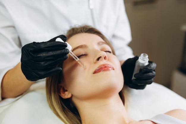 Cosmetologo che applica acqua di oli vitaminici essenziali di essenza di siero sul viso per migliorare la pelle del cliente.