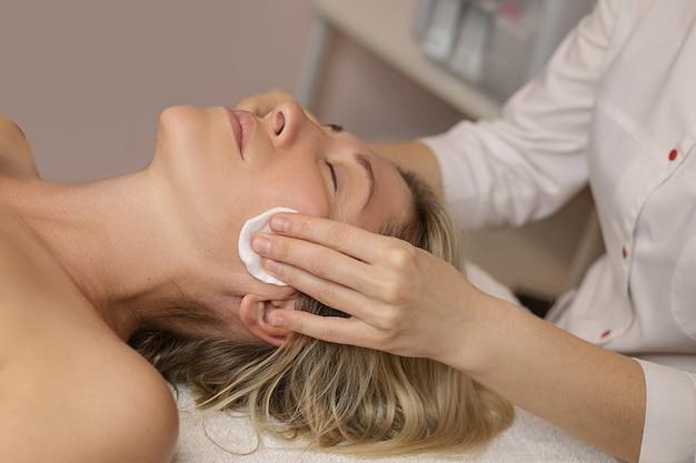 Cosmetologo che pulisce la pelle del cliente femminile di 35 anni con tamponi di cotone, lozione prima della procedura cosmetica nel salone della spa
