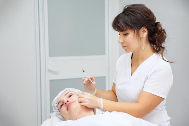 Il cosmetologo esegue procedure mediche con filler al collagene
