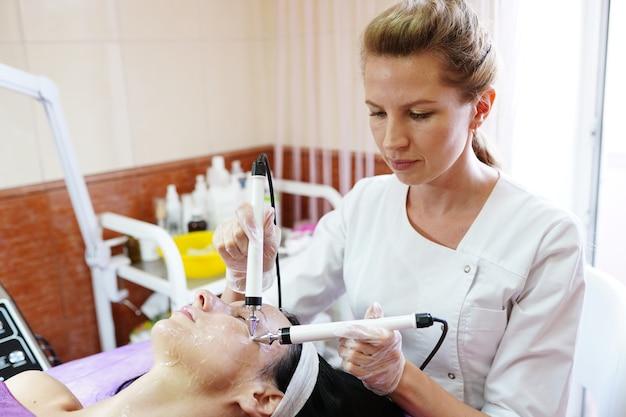 Cosmetologo dong la procedura della terapia microcorrente. procedura di estetista per il viso.