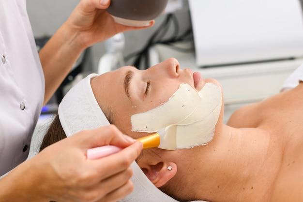 Le mani del cosmetologo applicano una maschera di alginato peeling detergente bianco