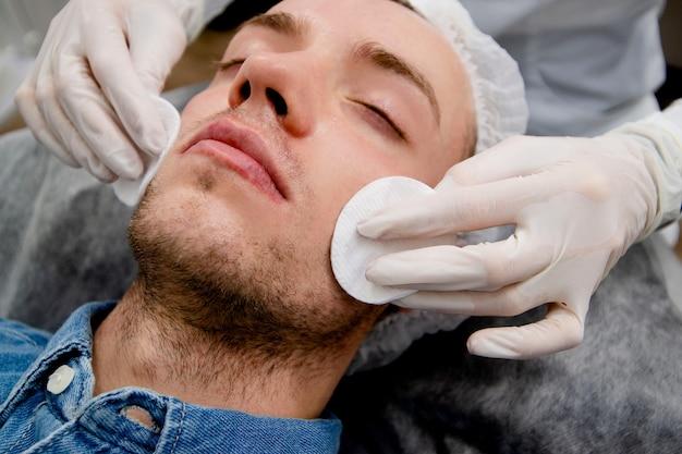 Il cosmetologo sta pulendo il viso dell'uomo usando un detergente e pastiglie per rimuovere l'acne e le cicatrici dal viso.
