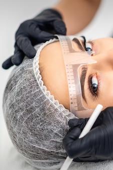 Il cosmetologo sta misurando con il righello le sopracciglia della giovane donna caucasica prima del tatuaggio di trucco permanente