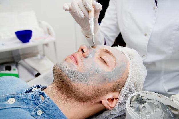 Il cosmetologo sta mettendo la maschera nera sul viso del giovane nel salone di bellezza.