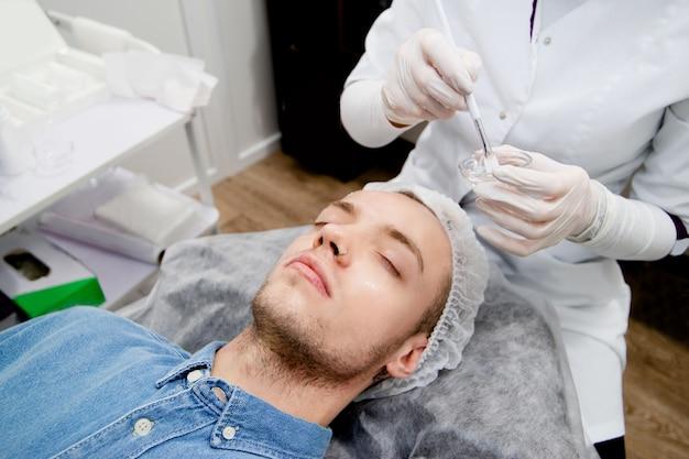 Il cosmetologo sta mettendo il sollevamento sul viso del giovane nel salone di bellezza.
