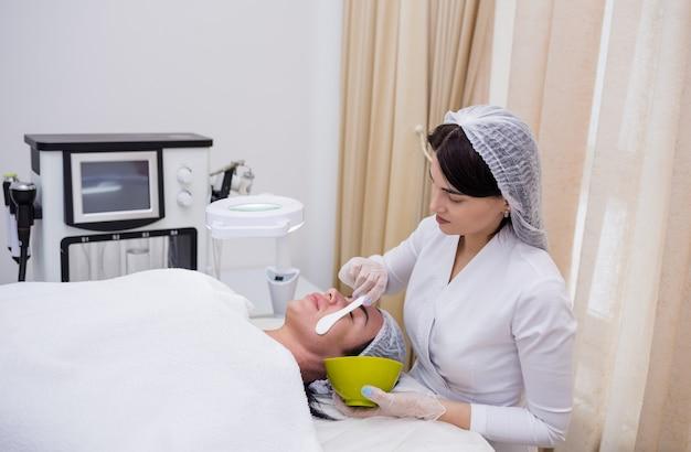 Il cosmetologo fa una maschera per il viso per un cliente sul divano Foto Premium