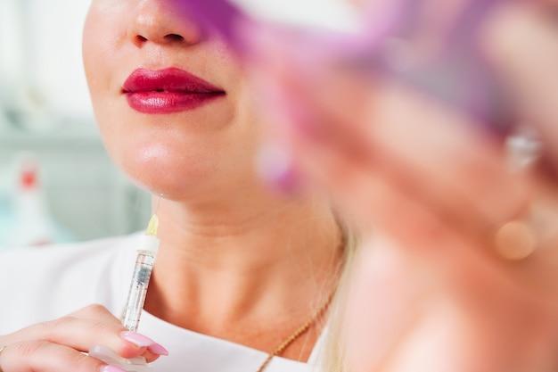 Il cosmetologo fa iniezioni lipolitiche per bruciare il grasso sul mento contro l'estetica femminile del doppio mento...