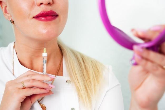 Il cosmetologo fa iniezioni lipolitiche per bruciare il grasso sul mento, sulle guance e sul collo di una donna contro ...
