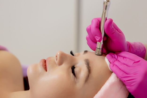 Il cosmetologo esegue la procedura di microdermoabrasione della pelle del viso di una bella e giovane donna in un salone di bellezza.