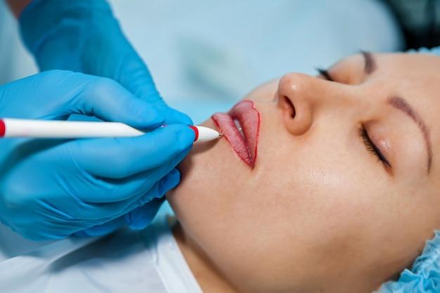 Cosmetologo, segna le matite sulle labbra per il trucco permanente labbra