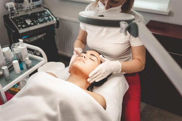 Il cosmetologo massaggia il viso del cliente
