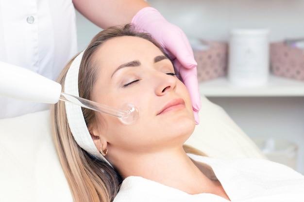 Il cosmetologo esegue una procedura di corrente pulsata per il viso di una giovane donna.