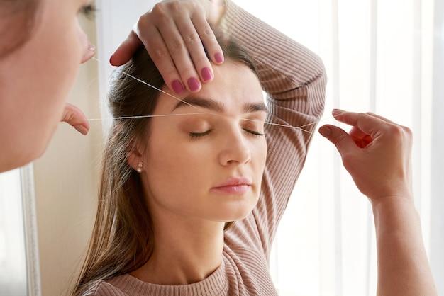Cosmetologo coglie le sopracciglia del cliente per filo nel salone di bellezza