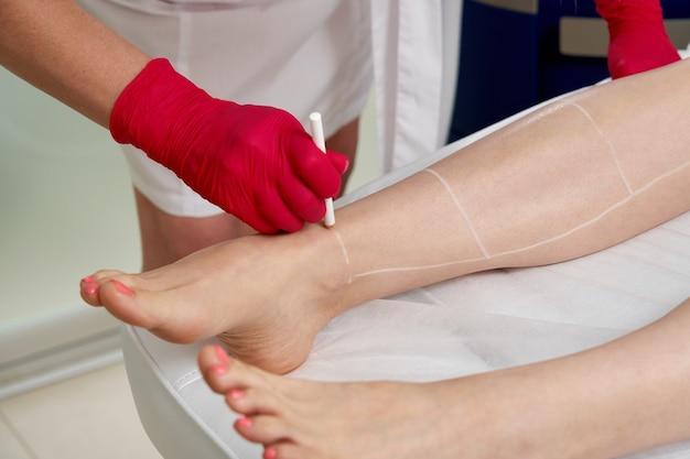 Cosmetologo che prepara paziente femminile per la depilazione laser sulle gambe nel salone spa