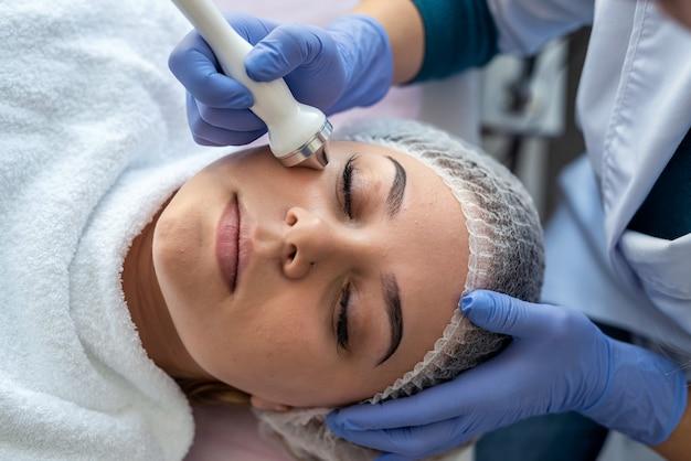 Cosmetologo che utilizza macchina di cavitazione ad ultrasuoni facendo massaggio terapia di sollevamento procedura