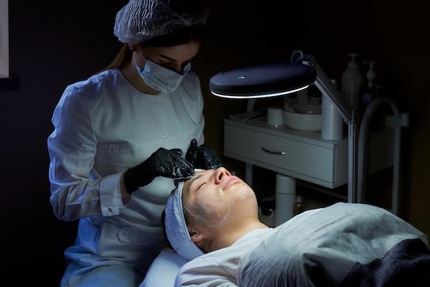Un cosmetologo che indossa una maschera e guanti medici usa e getta si strofina la crema sul viso di una donna per tonificare la pelle