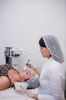 Un cosmetologo in uniforme bianca fa una maschera per il viso per un cliente