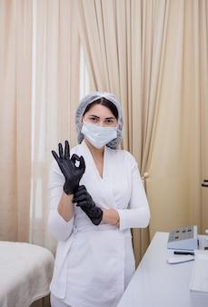 Un cosmetologo in uniforme bianca in piedi con un berretto e guanti neri
