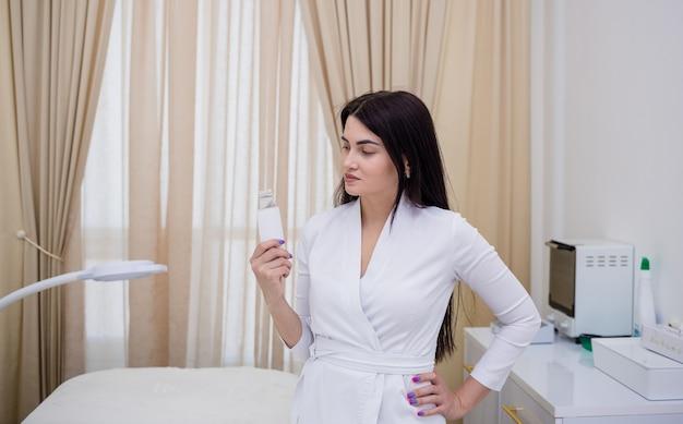 Il cosmetologo in uniforme bianca sta in piedi e tiene in mano un dispositivo di pulizia ad ultrasuoni in ufficio