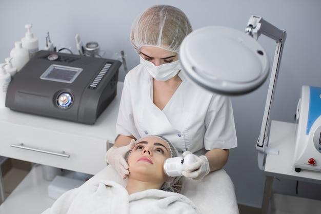 Cosmetologia. bella donna che riceve la cavitazione ad ultrasuoni della pelle del viso. primo piano del viso femminile che riceve cosmetici anti-invecchiamento utilizzando la macchina per cavitazione ad ultrasuoni. cura del corpo