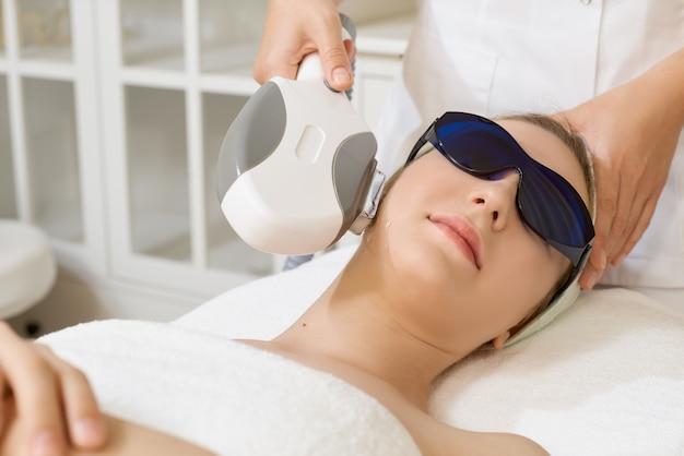 Cosmetologia. bella donna che riceve la procedura di rimozione dei capelli del laser al salone di bellezza.