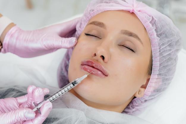 Procedura di cosmetologia per l'aumento delle labbra e la rimozione delle rughe per una giovane e bella ragazza. cosmetologia.