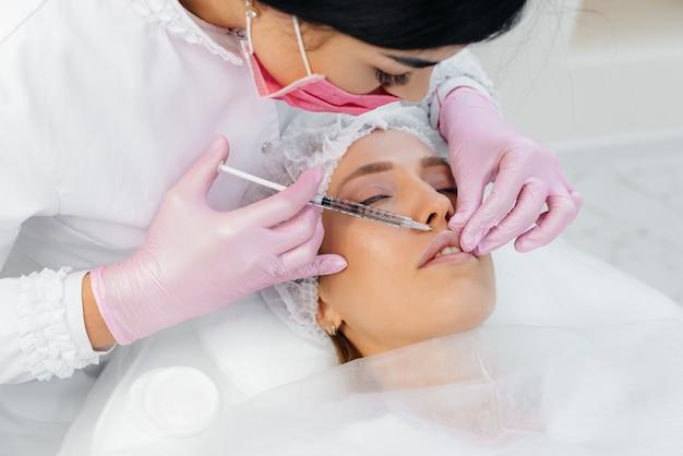 Procedura di cosmetologia per l'aumento delle labbra e la rimozione delle rughe per una giovane donna