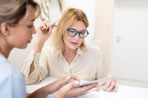 Specialista di cosmetologia rispondendo alle domande dei clienti sulla procedura di bellezza, donna matura in bicchieri leggendo attentamente l'accordo