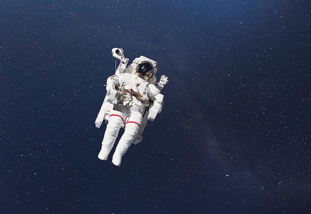 Un cosmonauta vola nello spazio esterno con stelle e sfondo di galassie con un raggio di luce. elementi di questa immagine forniti dalla nasa