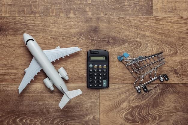 Calcolo dei costi di consegna aerea, acquisti, logistica. figurina di carrello della spesa, aereo, calcolatrice sul pavimento di legno.
