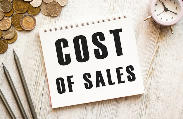 Costo di vendita testo su un foglio di blocco note. le monete sono sparse, matite su uno sfondo di legno grigio. concetto finanziario.