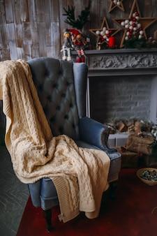 Poltrona accogliente con coperta calda si trova davanti a un camino