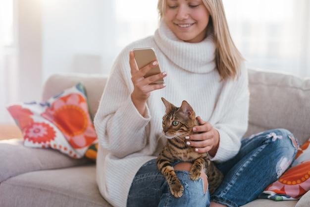 Ambiente familiare accogliente. animale domestico di famiglia. ragazza che accarezza il suo gatto bengala mentre guarda il suo telefono.