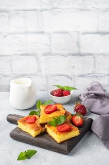 Casseruola di ricotta con fragole e menta. delizioso dessert fatto in casa a base di cagliata e frutti di bosco freschi con panna. sfondo grigio cemento, copia dello spazio.