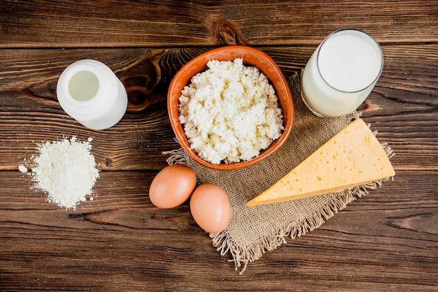 Ricotta, formaggio e bicchiere di latte su fondo di legno. latticini.