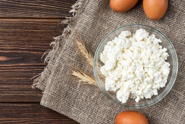 Ricotta, uova e latte su fondo di legno scuro.