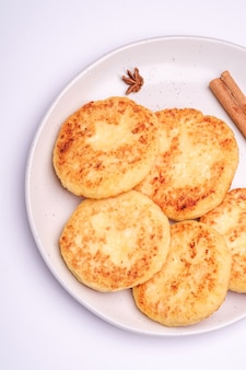 Frittelle di ricotta. atmosfera della colazione di natale con anice e cannella su superficie bianca, vista dall'alto